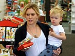 Juggling act: With her growing two-year-old balanced on one hip, the Disney star managed to carry both her bright red wallet and a big container of gummy worms in one hand as she headed to the check out