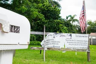 A sign stands at 1448 NW 103rd St. in Miami to let passers-by know the government demolished the house even though the owner was on active military duty.