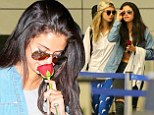 Holiday romance? Selena Gomez holds on to a rose as she and Cara Delevingne land in LA after their whirlwind trip to France