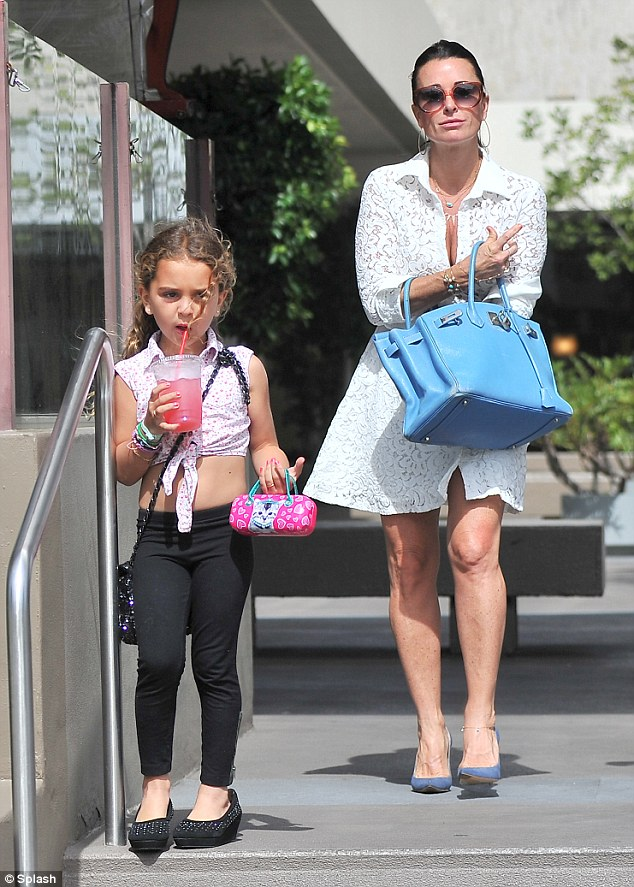 Cooling off: Portia sipped on a pink beverage which matched her adorable handbag