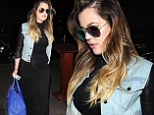 Khloe Kardashian slenderizes her curves in a form-fitting black dress as she rushes to catch a flight out of LAX