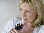 A middle aged woman drinking glass of wine.   Image by   KMSS/Corbis