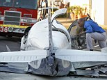 One dead: An aviation safety inspector looks inside the cockpit of a small airplane after it crashed in a shopping center parking lot