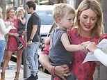 Keeping him close! Hilary Duff carries son Luca while flashing her pins in cute red dress following dinner with estranged husband Mike Comrie