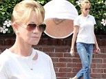 It's still there! Melanie Griffiths 'Antonio' tattoo peaks out from under her T-shirt sleeve despite removal efforts as she goes for stroll in Beverly Hills