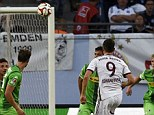 Golazo: Robert Lewandowski guides the ball over the 'keeper and a crowd of defenders with a chip