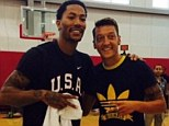 All smiles: Arsenal midfielder Mesut Ozil (right) poses for a picture with Chicago Bulls star Derrick Rose