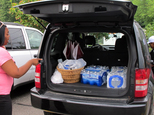 Aundrea Simmons stands next to her minivan with cases of bottled water she bought after Toledo warned residents not to use its water, Saturday, Aug. 2, 2014 ...