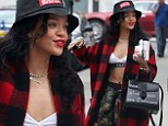 Rihanna shows off her flat stomach in a bra top as she juggles a yogurt, phone and book in her hand