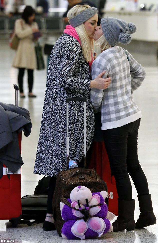 Sealed with a kiss! The new Mrs and Mrs Hart looked affectionate when they were spotted arriving at Sydney Airport on Sunday as they returned from Auckland