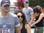 Hard to miss: Mila Kunis showed off her growing belly in a sleeveless black shirt as she and her fiance Ashton Kutcher went art shopping in Brentwood, California on Saturday