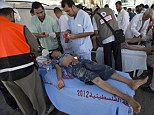 A Palestinian boy, wounded following an Israeli military strike, is treated at a hospital in the Gaza Strip, while at least 10 people were killed in a fresh strike on a UN school on Sunday