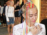 A colourful character! Miley Cyrus shows off rainbow hair braids as she saunters around in New York