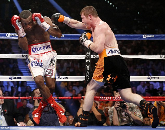 On the attack: Alvarez (right) swings at Lara as the Mexican charges forward during the fight