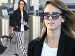 Jessica Alba landed at the airport in New York City on Monday. Her ensemble included a white t-shirt with 'Sleep When You're Dead' emblazoned across the front, a black blazer, black and white striped Beetlejuice inspired trousers, matching striped socks and shiny black loafers.