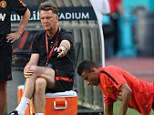 Push up: Van Gaal makes a point as the players perform one-handed press-ups using basketballs