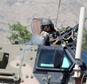 A NATO soldier opens fire in an apparent warning shot in the vicinity of journalists near the main gate of Camp Qargha, west of Kabul, Afghanistan, Tuesday, ...