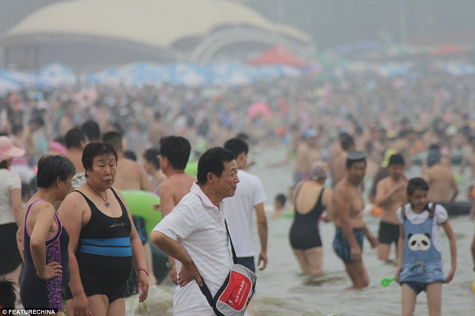 Relaxed: Crowds of 100,000 routinely swarm the No 1 beach in Qingdao on weekends during the summer months