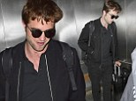 There's no disguising that handsome face! Robert Pattinson attempts to go incognito as he arrives at LAX