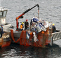 The wreckage of a plane is hauled onto a fishing boat off the southern point of Great Barrier Island near Auckland, New Zealand, Thursday, Aug. 7, 2014. Auth...