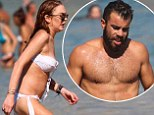 Lindsay Lohan continues to parade her bikini body as she hits the beach with hunky man in Greece