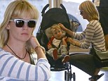 Family first: Janaury Jones was seen brushing her son Xander's hair as the two landed at Los Angeles International Airport on Thursday