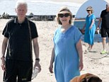 A very casual Bill and Hillary Clinton enjoy some downtime by walking their dogs on the beach in the Hamptons