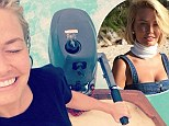 Loving life out at sea! Model Lara Bingle looks on top of the world as she steers a motorised boat after freezing on a beach photoshoot