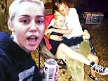 'White trash rager': Miley Cyrus knocks back beers and moonshine with her uncle and friends at backyard fireside party