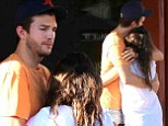 Cuddles and kebabs! Pregnant Mila Kunis wraps Ashton Kutcher in a tender hug after he takes her out for Greek food
