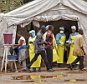 In this photo taken Saturday, Aug. 9, 2014, health workers, center rear, screen people for the deadly Ebola virus before entering the Kenema Government Hospital in Kenema, 300 kilometers, (186 miles) from the capital city of Freetown, Sierra Leone.  Over the decades, Ebola cases have been confirmed in 10 African countries, including Congo where the disease was first reported in 1976. But until this year, Ebola had never come to West Africa.  (AP Photo/ Michael Duff)