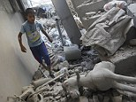 A Palestinian boy walks past a rocking horse as he inspects his house after it was hit by an Israeli military strike