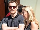 Michael Fassbender shows off his muscular arms as he pulls a Bono by wearing rose-tinted sunglasses for a day out in NYC with a blonde companion