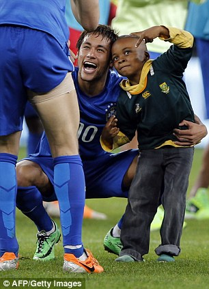 Say cheese: Neymar poses with a young South African fan who invaded the pitch