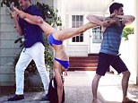 Pretty impressive: Hilaria Baldwin performs her latest yoga pose in high heels and does the splits while doing a handstand