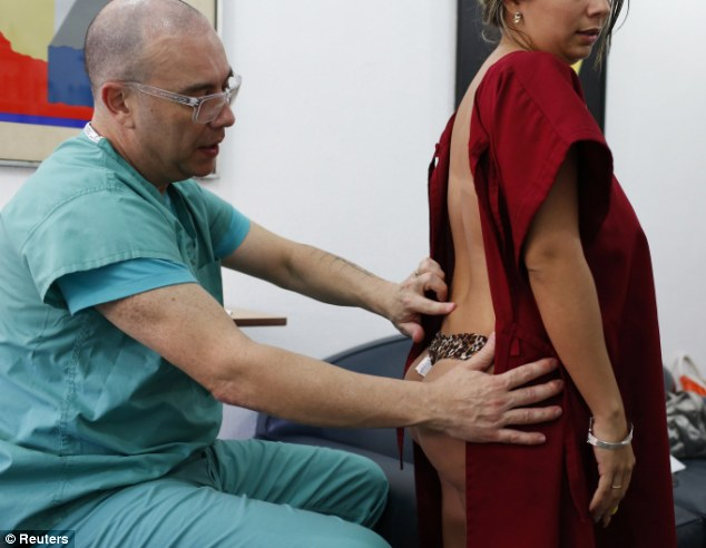 Implant issues: Venezuelan plastic surgeon Daniel Slobodianik examines a patient who had paid to have liquid silicone injected into her buttocks which has travelled up to her lower back