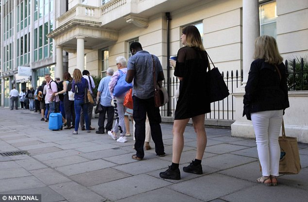 """National News and Pictures Date: 13/06/14 PH: Johnathan Adam Davies Pictured: Holiday makers queue outside the Passport Office in London Caption: Travellers queue outside the Passport Office in London after Home Secretary, Theresa May, promised free fast-tracking for holiday makers and business people with """"urgent need to travel"""". The announcement comes after a backlog of thousands of applications built up, leaving people facing weeks waiting or paying £55.50 extra to get their passport on time. Victoria, London."""