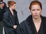 The great cover up! Amy Adams keeps dry with a raincoat as she heads to the gloomy Detroit set of Batman V Superman to reprise her role of Lois Lane