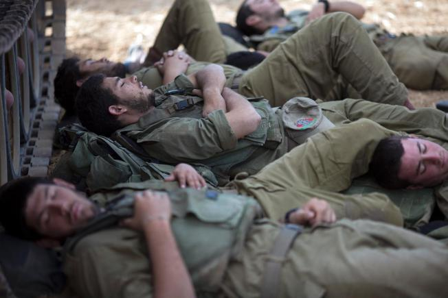 Israeli soldiers sleep in the shade of a military vehicle near the Israel-Gaza border early Tuesday, July 15, 2014.