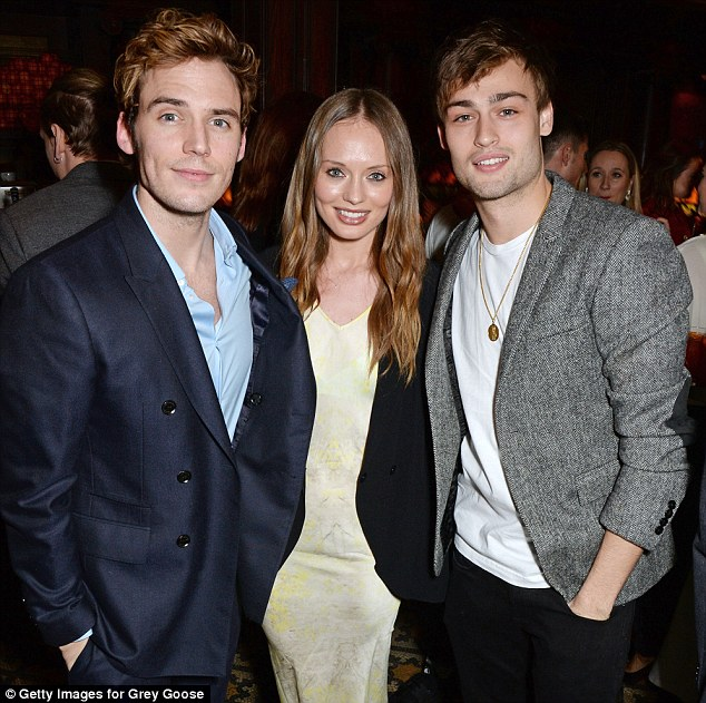 A happy trio: Sam Claflin and his wife Laura Haddock stood chatting with movie star Douglas Booth who posed with his hand in his pocket