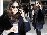 Nicole Trunfio sports a chic faux-fur shawl and shows off off her slim pins in leather trousers at Melbourne airport