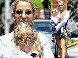 Actress Elizabeth Berkley carries her two-year-old son Sky to the car in her arms