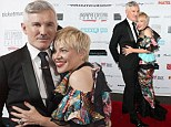 Not letting it rain on their parade! Catherine Martin cuddles up to Great Gatsby director husband Baz Luhrmann as they brave wild Sydney weather to attend Helpmann Awards