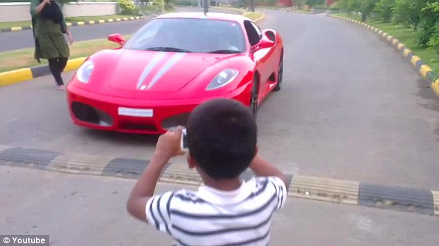 A friend of the under-age driver takes a picture on his phone as the Ferrari F430 pulls up before taking off round the block in the wealthy Thrissur area