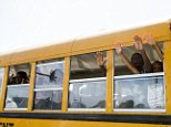 """A school bus full of children gesture and chant """"hands up, don't shoot"""" as they drive past the scene of where, according to local media, police shot dead a 23-year-old man wielding a knife in the St Louis area August 19, 2014. The shooting follows a night where dozens of people had been arrested, marking the latest outbreak of rancor in the St. Louis suburb where calls for peaceful protests have been overshadowed by episodes of looting, arson and clashes with police over the last 10 days. REUTERS/Lucas Jackson (UNITED STATES - Tags: CIVIL UNREST CRIME LAW EDUCATION) - RTR430JF"""