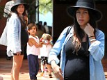 Embracing the bump! Kourtney Kardashian displays her blossoming belly in skintight black dress during family outing