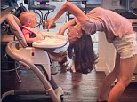 Dinner and a show! Hilaria Baldwin continues her fun and inventive 'yoga posture every day' challenge by feeding her daughter Carmen upside down