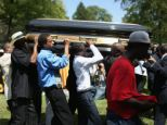 Pallbearers carry the casket of Michael Brown at St Peter's cemetery