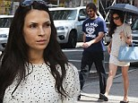 Famke Janssen keeps shaded from UV rays under frilly 'sunbrella' on stroll with longtime love Cole Frates and their dog