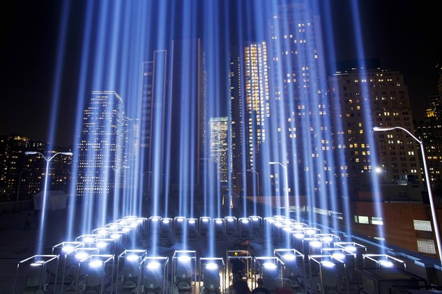 FILE- In this Sept. 10, 2013 file photo, the Tribute in Light rises above buildings during a test in New York. While the plaza at the National September 11 M...